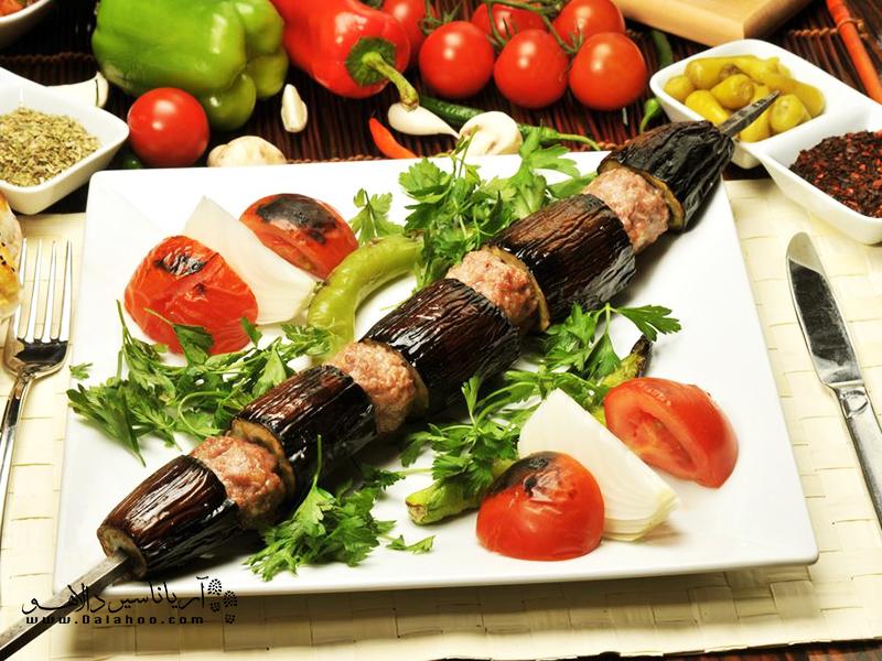کنار هر بادمجان، گوجه و فلفل قرمز هم سیخ میکنند تا طعم این کباب بینظیر چندین برابر شود.